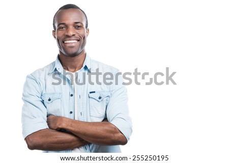 Successful and happy man. Handsome young black man keeping arms crossed and smiling at camera while standing against white background  - stock photo