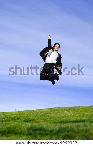successful and happy young adult businessman running and jumping in the green field - stock photo