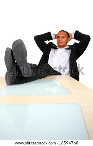Successful And Relaxed A young satisfied businessman sitting by desk at office feet on table thinking.