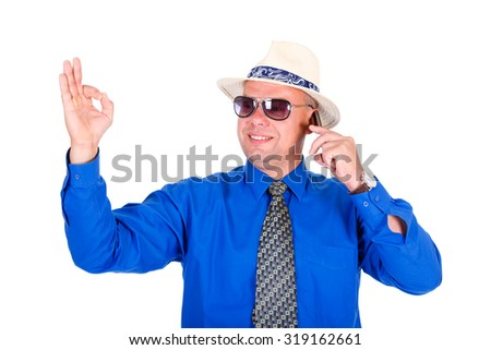 Successful and smiling businessman in blue shirt, tie, sunglasses and white hat. Speaking by cell mobile phone and shows gesture OK. Isolated white background, Concept of leadership and success - stock photo