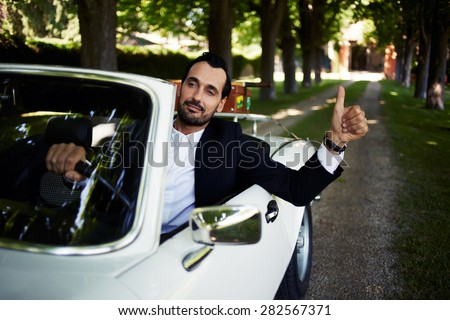 Successful and wealthy businessman sitting behind steering wheel of luxury cabriolet car on countryside road, confident handsome man sits in his new convertible car doing super gesture with the finger  - stock photo