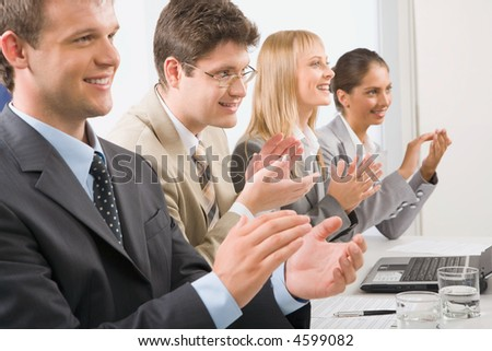 Successful applauding young people sitting at the table in the office