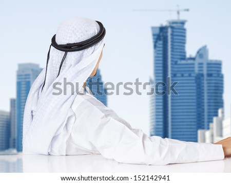 Successful Arab businessman looking out the window of his office. - stock photo