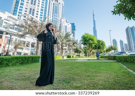 Successful Arab woman. Arab businesswoman wearing hijab talking on cell phone and shows the thumb up against the skyscrapers of Dubai. The woman is dressed in a black abaya - stock photo