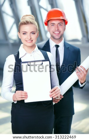 Successful architects are ready to sign a contract with their customer. They are standing and smiling. The woman is showing a folder of documents. The man is holding a blueprint - stock photo