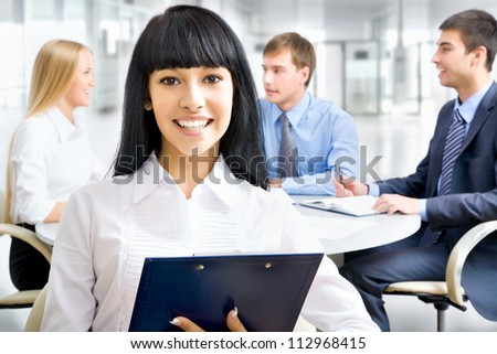 Successful asian business woman with her staff in background at office - stock photo
