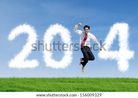 Successful asian businessman is jumping over grass with clouds of 2014
