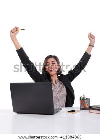 Successful Asian female office worker raising both arms in happiness while looking at her laptop screen, isolated on white background - stock photo