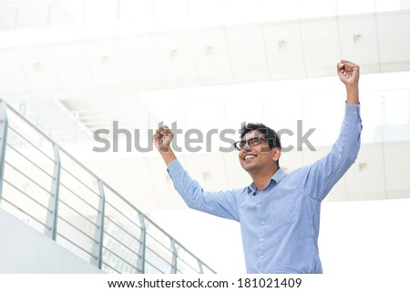 Successful Asian Indian businessman with arms up celebrating his victory, modern office building as background. - stock photo