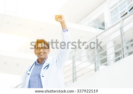 Successful Asian Indian medical doctor with arm up celebrating his victory, hospital building as background. - stock photo