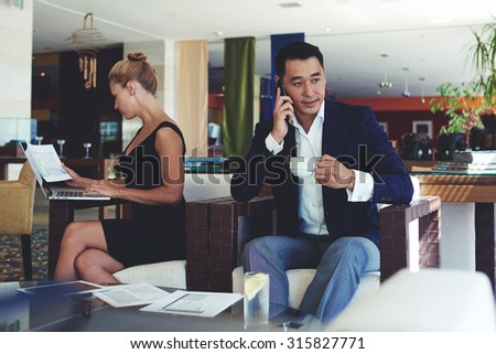 Successful asian man talking on smart phone and enjoying coffee whereas his female colleague using laptop computer while reading monthly reports on papers, business people working in office space - stock photo