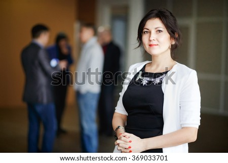 Successful attractive business woman boss brunette with kind eyes stands inside office building, leadership concept, candid portrait. Cute young chief female posing. In background man discussing. - stock photo