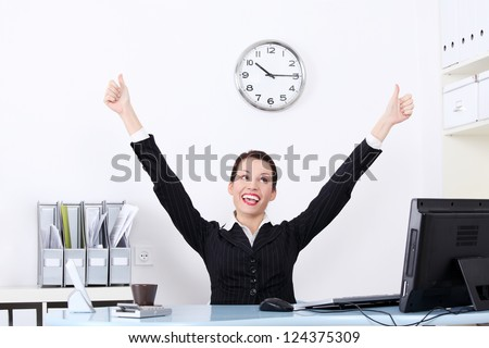 Successful attractive businesswoman with hands up at the desk in her office. - stock photo