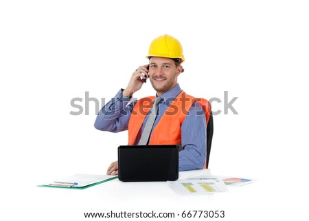 Successful attractive caucasian man architect with safety helmet in the office working with laptop and talking by phone. Studio shot. White background. - stock photo