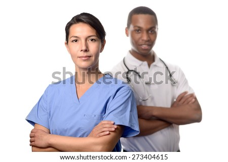 Successful attractive female doctor or surgeon in scrubs standing with folded arms in front of an African male doctor or consultant conceptual of an expert medical team, on white - stock photo