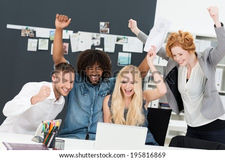 Successful attractive young multiethnic business team celebrating a victory cheering and pumping the air with their fists - stock photo