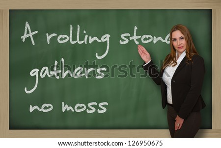Successful, beautiful and confident woman showing A rolling stone gathers no moss on blackboard - stock photo