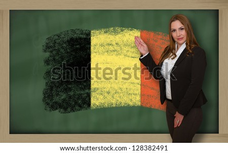Successful, beautiful and confident woman showing flag of belgium on blackboard for marketing research, presentation and tourist advertising - stock photo
