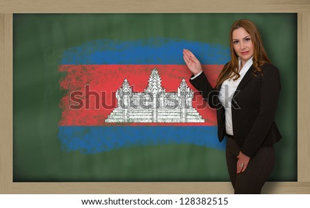 Successful, beautiful and confident woman showing flag of cambodia on blackboard for marketing research, presentation and tourist advertising - stock photo