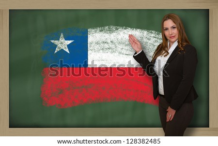 Successful, beautiful and confident woman showing flag of chile on blackboard for marketing research, presentation and tourist advertising - stock photo