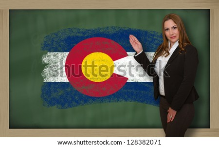 Successful, beautiful and confident woman showing flag of colorado on blackboard for marketing research, presentation and tourist advertising - stock photo