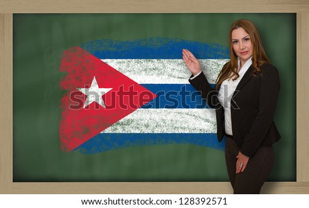 Successful, beautiful and confident woman showing flag of cuba on blackboard for marketing research, presentation and tourist advertising - stock photo