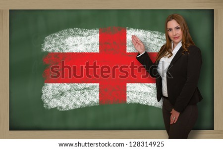Successful, beautiful and confident woman showing flag of england on blackboard for marketing research, presentation and tourist advertising - stock photo