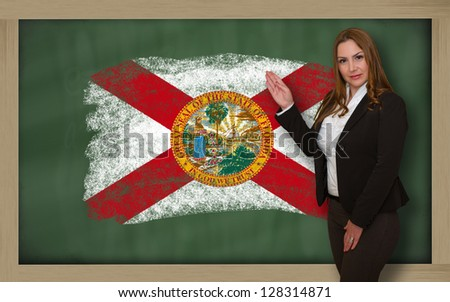 Successful, beautiful and confident woman showing flag of florida on blackboard for marketing research, presentation and tourist advertising - stock photo