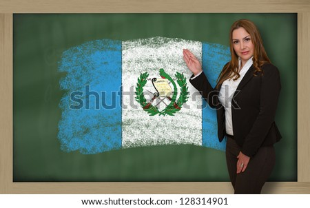 Successful, beautiful and confident woman showing flag of guatemala on blackboard for marketing research, presentation and tourist advertising - stock photo