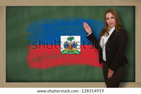 Successful, beautiful and confident woman showing flag of haiti on blackboard for marketing research, presentation and tourist advertising - stock photo