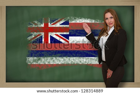 Successful, beautiful and confident woman showing flag of hawaii on blackboard for marketing research, presentation and tourist advertising - stock photo