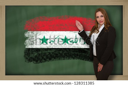 Successful, beautiful and confident woman showing flag of iraq on blackboard for marketing research, presentation and tourist advertising - stock photo
