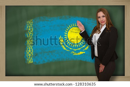 Successful, beautiful and confident woman showing flag of kazakhstan on blackboard for marketing research, presentation and tourist advertising - stock photo