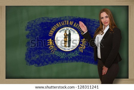 Successful, beautiful and confident woman showing flag of kentucky on blackboard for marketing research, presentation and tourist advertising - stock photo