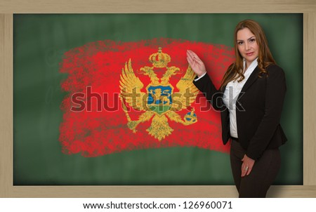Successful, beautiful and confident woman showing flag of montenegro on blackboard for marketing research, presentation and tourist advertising - stock photo