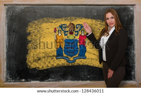Successful, beautiful and confident woman showing flag of new jersey on blackboard for marketing research, presentation and tourist advertising - stock photo