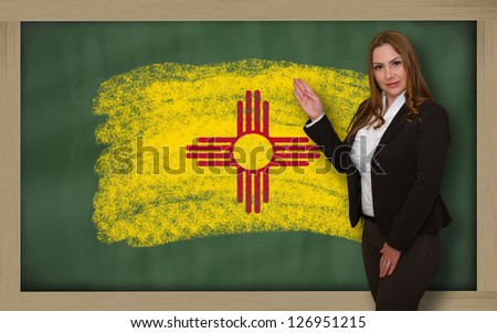 Successful, beautiful and confident woman showing flag of new mexico on blackboard for marketing research, presentation and tourist advertising - stock photo