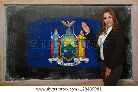 Successful, beautiful and confident woman showing flag of new york on blackboard for marketing research, presentation and tourist advertising - stock photo