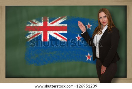 Successful, beautiful and confident woman showing flag of new zealand on blackboard for marketing research, presentation and tourist advertising - stock photo