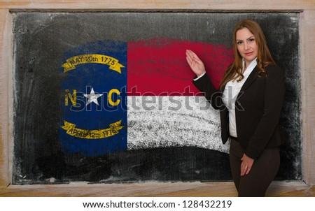 Successful, beautiful and confident woman showing flag of north carolina on blackboard for marketing research, presentation and tourist advertising - stock photo