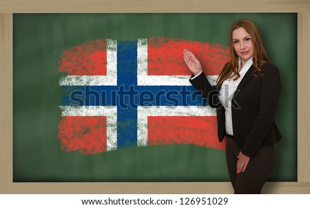 Successful, beautiful and confident woman showing flag of norway on blackboard for marketing research, presentation and tourist advertising - stock photo