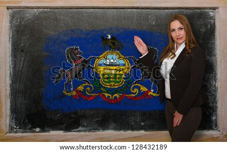 Successful, beautiful and confident woman showing flag of pennsylvania on blackboard for marketing research, presentation and tourist advertising - stock photo