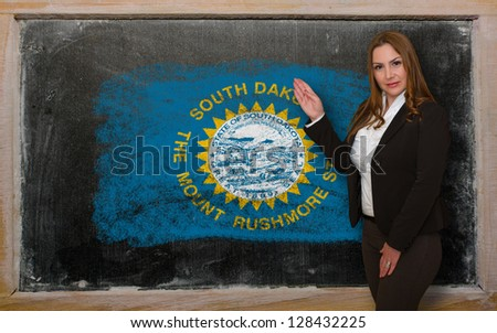 Successful, beautiful and confident woman showing flag of south dakota on blackboard for marketing research, presentation and tourist advertising - stock photo
