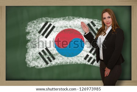Successful, beautiful and confident woman showing flag of south korea on blackboard for marketing research, presentation and tourist advertising - stock photo