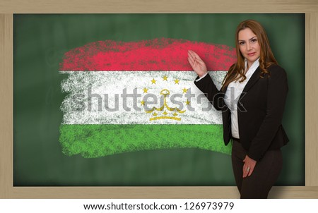 Successful, beautiful and confident woman showing flag of tajikistan on blackboard for marketing research, presentation and tourist advertising - stock photo