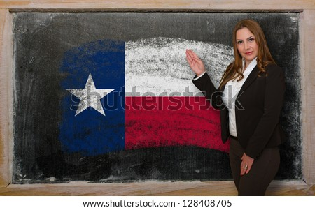 Successful, beautiful and confident woman showing flag of texas on blackboard for marketing research, presentation and tourist advertising - stock photo