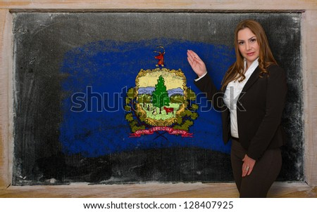 Successful, beautiful and confident woman showing flag of vermont on blackboard for marketing research, presentation and tourist advertising - stock photo