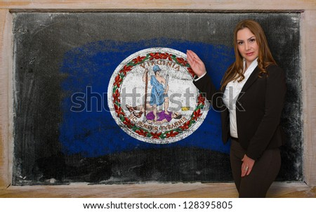 Successful, beautiful and confident woman showing flag of virginia on blackboard for marketing research, presentation and tourist advertising - stock photo
