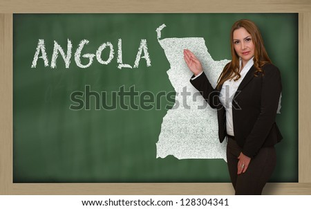 Successful, beautiful and confident young woman showing map of angola on blackboard for presentation, marketing research and tourist advertising - stock photo