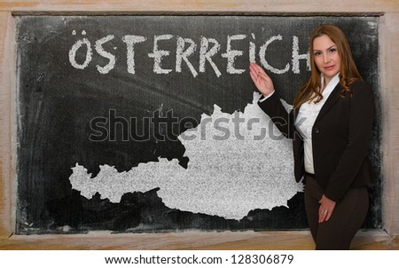 Successful, beautiful and confident young woman showing map of austria on blackboard for presentation, marketing research and tourist advertising - stock photo